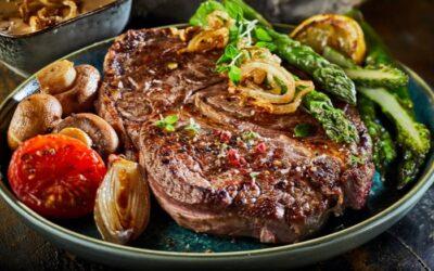 Grasgevoerde rib-eye steak met aardappelpuree en geroosterde groene asperges